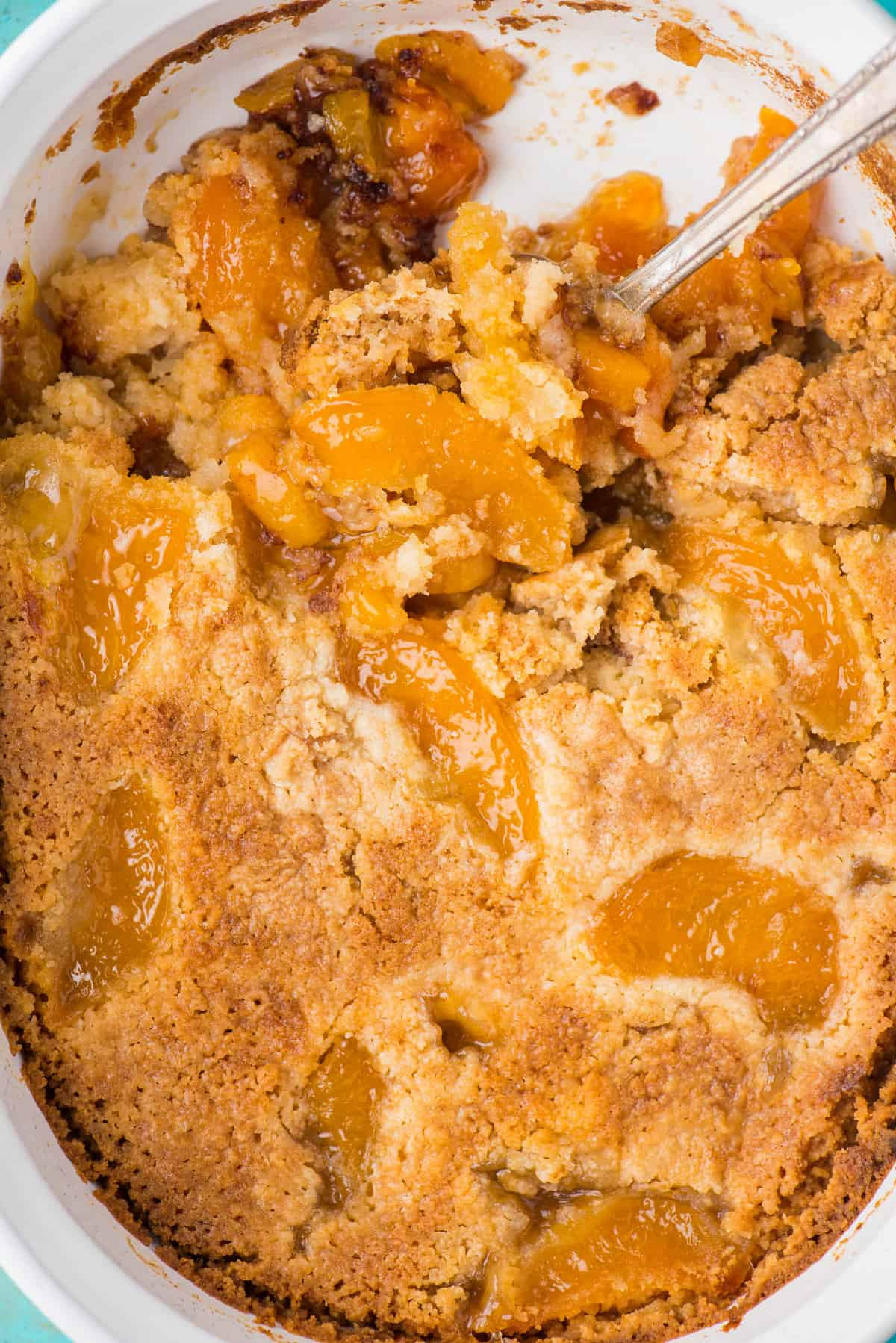peach dump cake with spoon in white pan