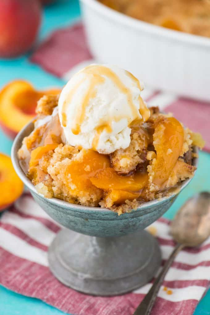 peach dump cake in metal bowl with scoop of vanilla ice cream on top