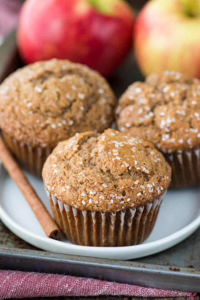 three apple muffins on white plate with cinnamon stick