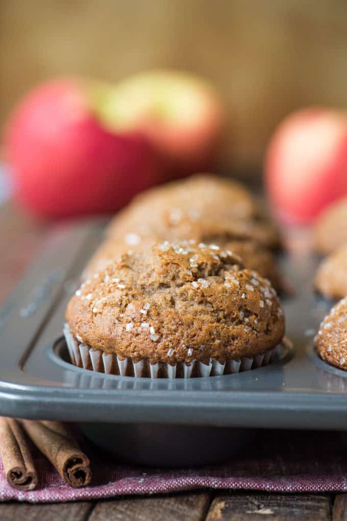 applesauce muffins in metal muffin pan with apples in background