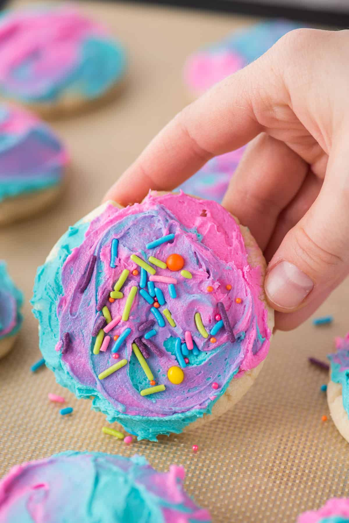hand holding frosted sugar cookie with tie dye frosting and colorful sprinkles