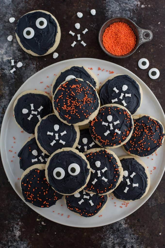halloween sugar cookies with black frosting and various sprinkles on white plate on black background