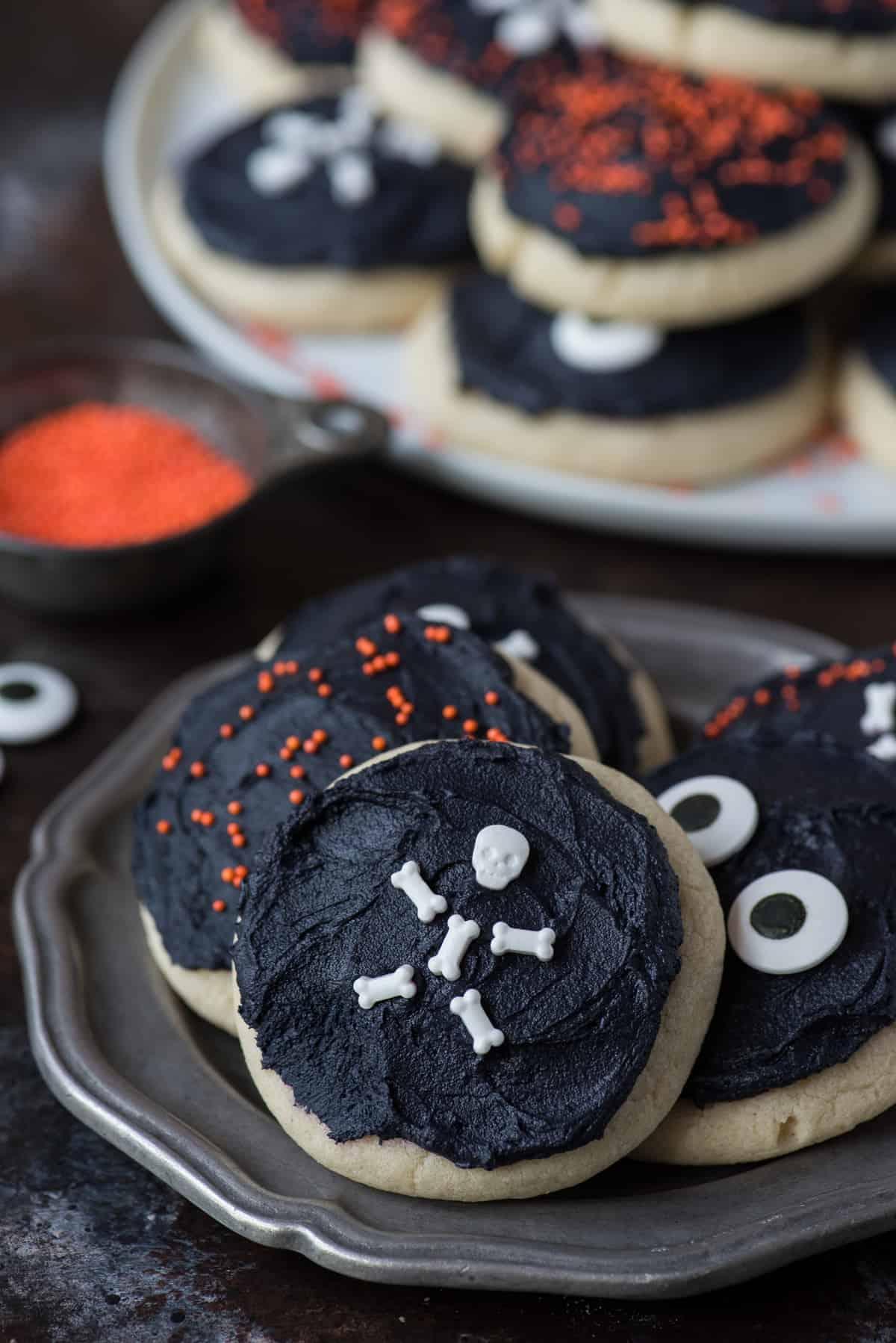halloween sugar cookies with black frosting and skeleton sprinkles on a metal plate