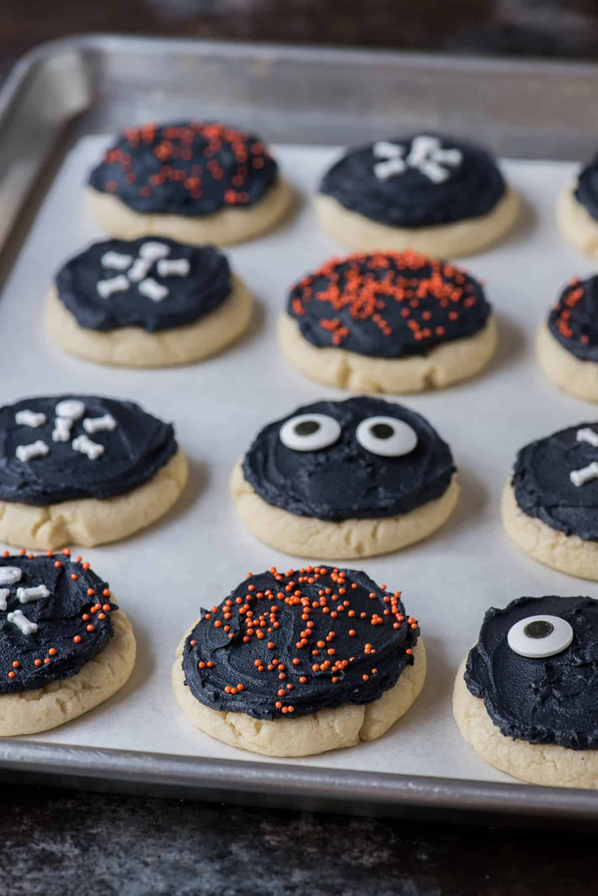 halloween cookies with black frosting and different types of sprinkles on baking sheet on black background