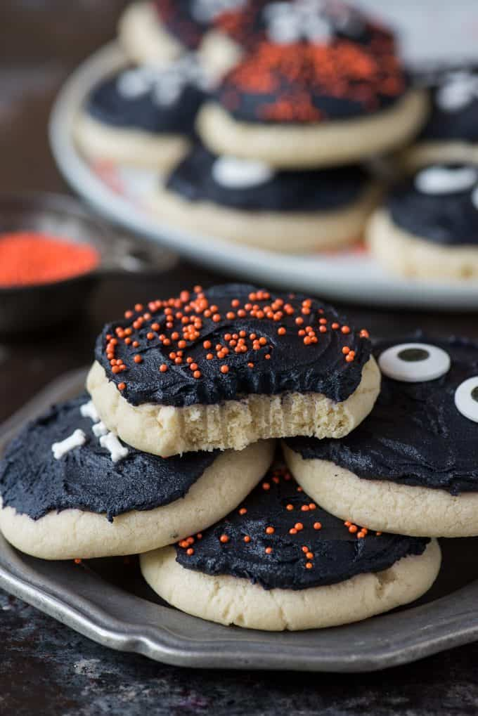 halloween sugar cookies stacked on a metal plate with bite removed from top cookie
