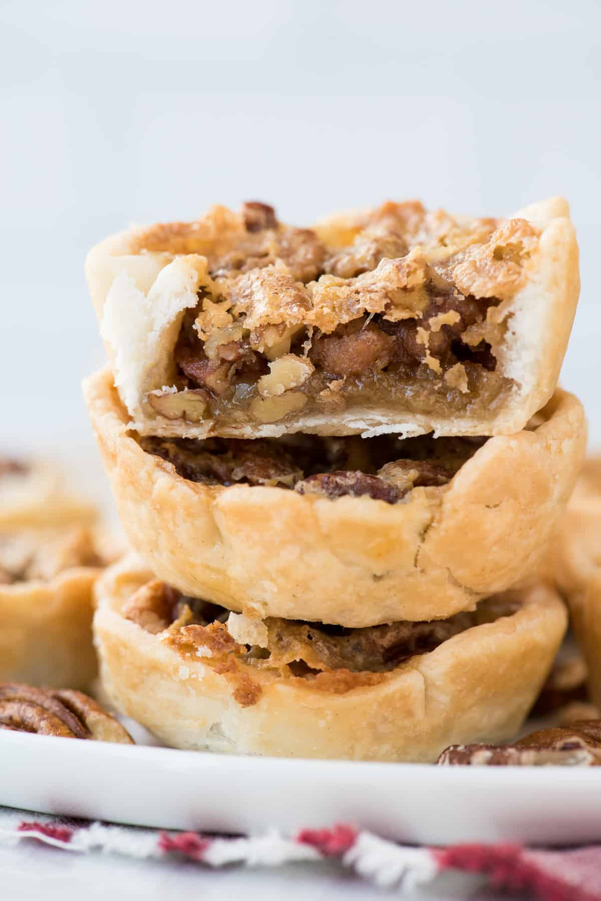 three mini pecan pies stacked on top of each other with bite removed from top pie