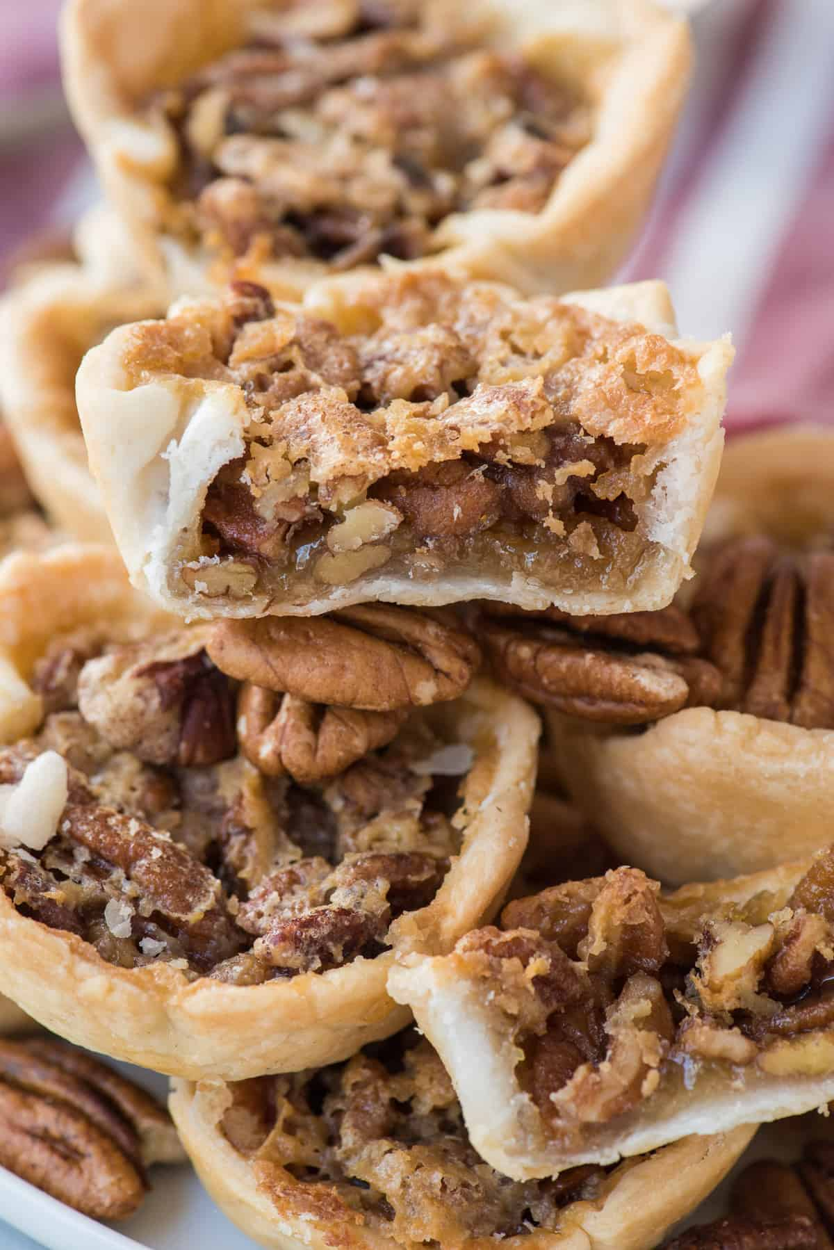 mini pecan pies in a pile with bite removed from the center pie