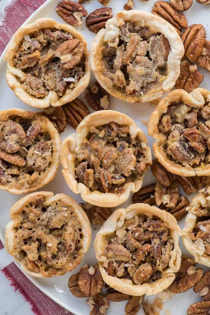 aerial shot of 8 mini pecan pies on white tray with red linen