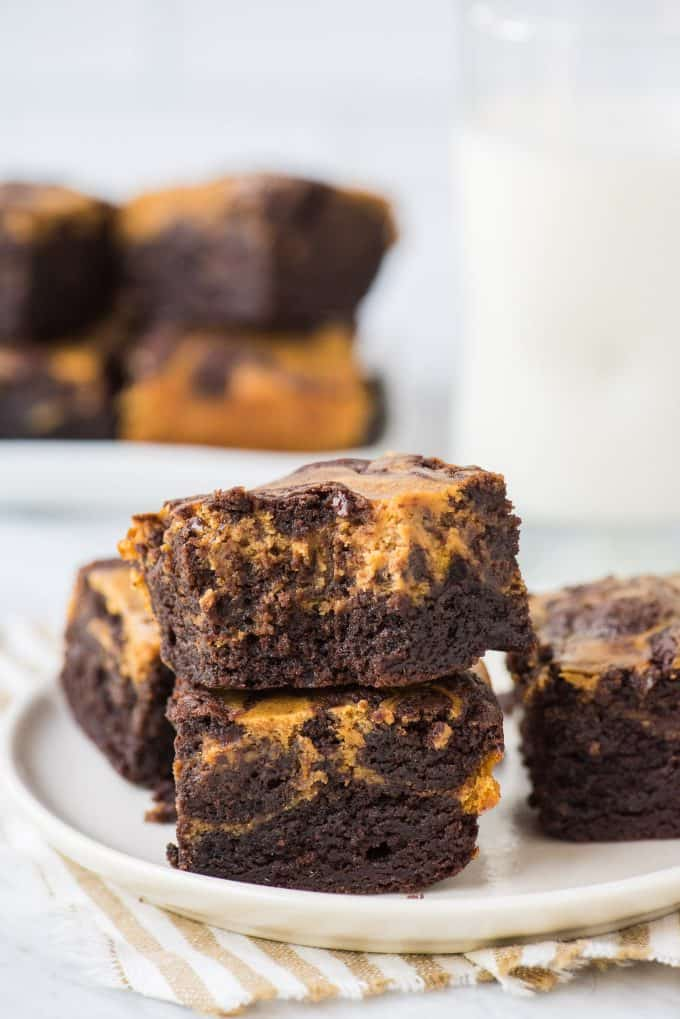 2 pumpkin cheesecake brownies stacked on top of each other on a round cream plate with striped linen underneath the plate