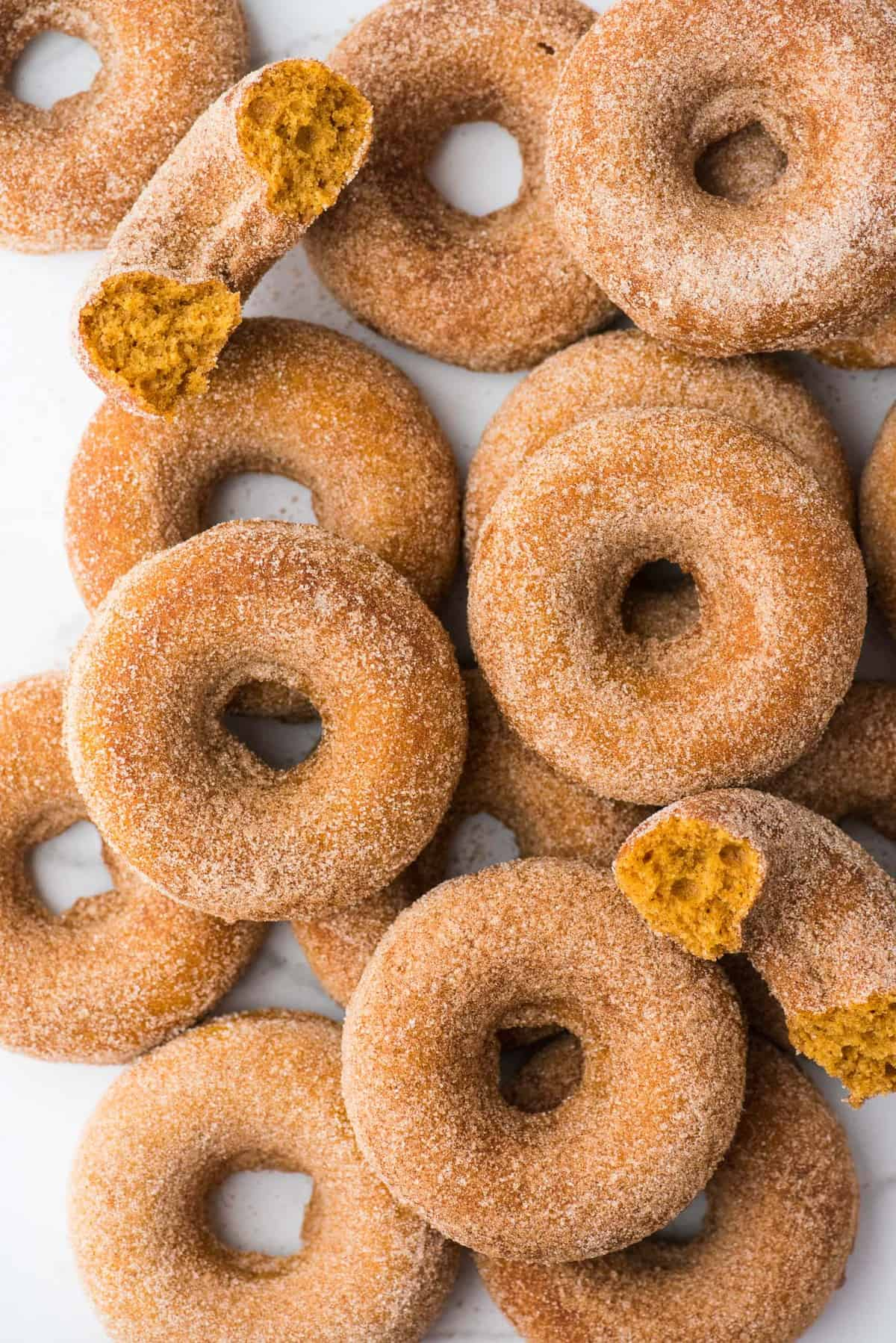 pumpkin donuts arranged in a pile on a white background