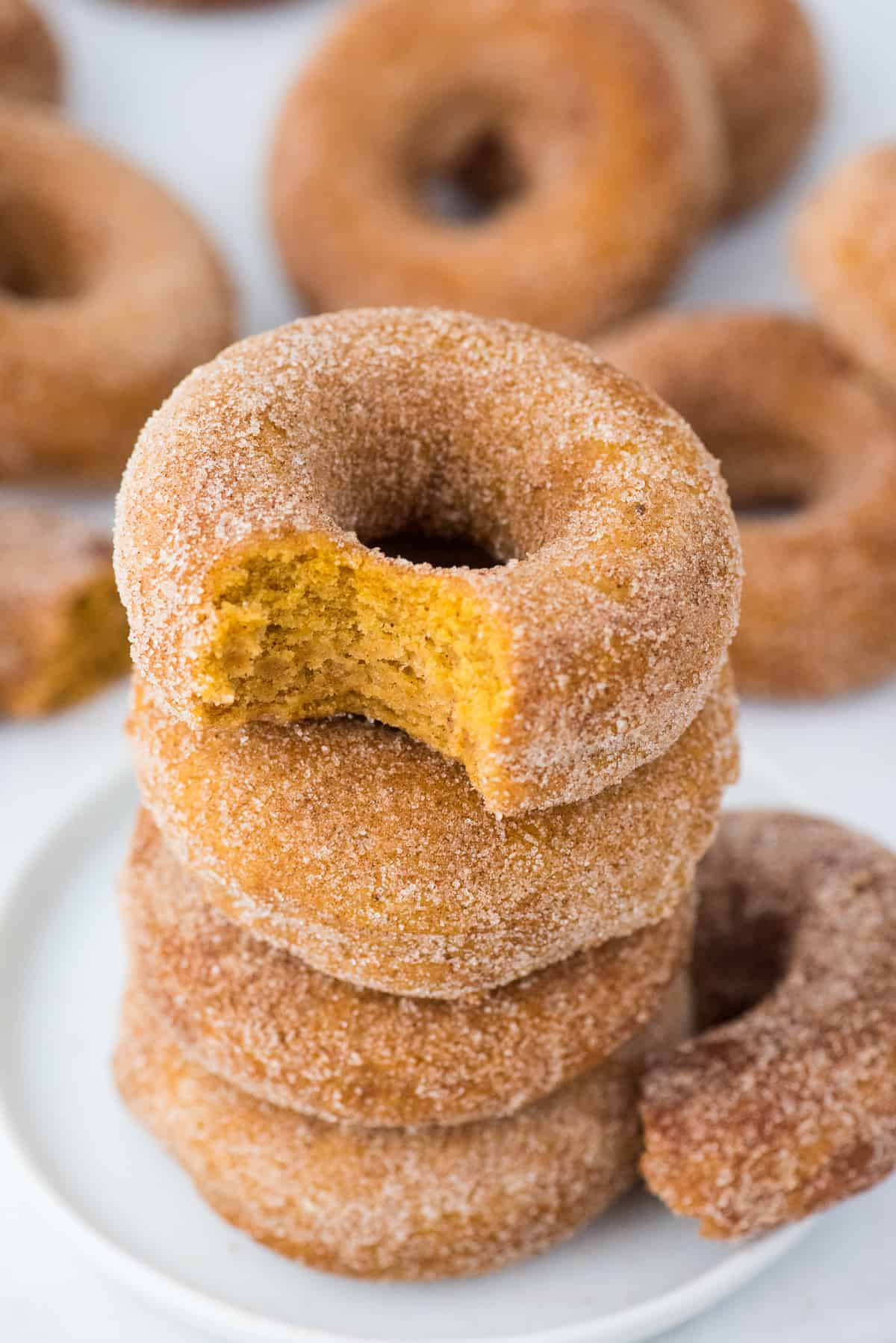4 pumpkin spice donuts stacked on a white plate. Top donut has a bite removed.