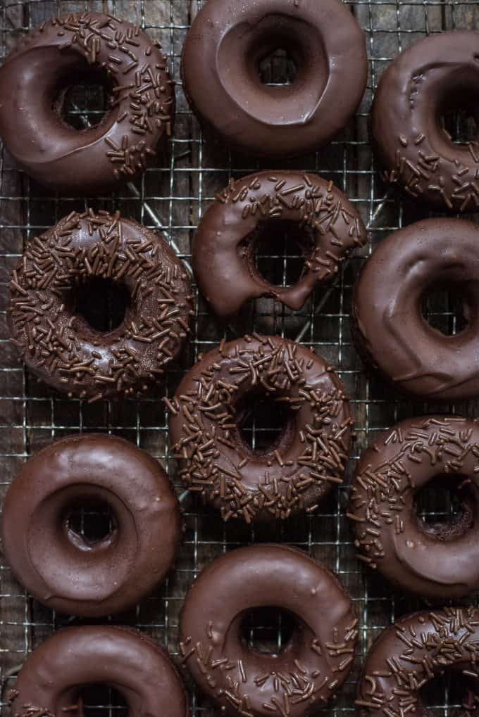 chocolate donuts with chocolate frosting in a line on metal cooling rack on dark background