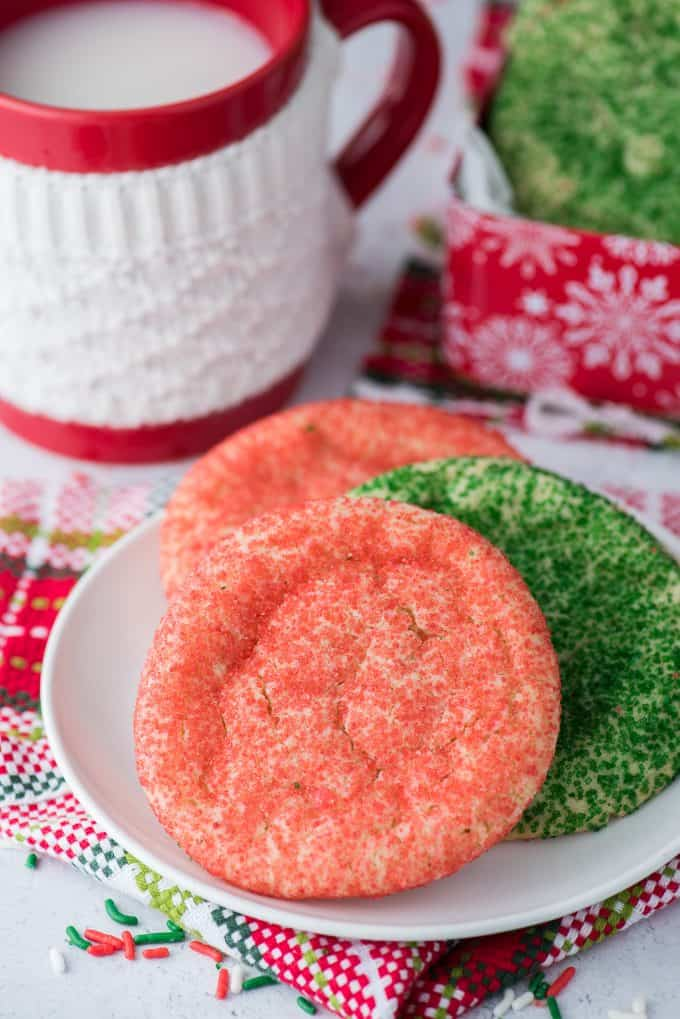 red and green christmas cookies on white plate with red mug in background
