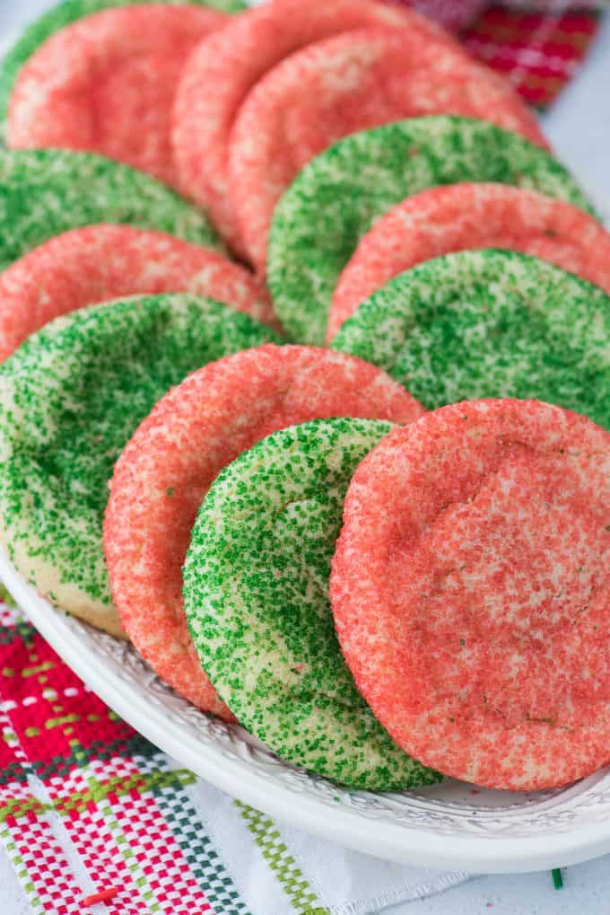 red and green sugar cookies on white plate with christmas napkin in the background