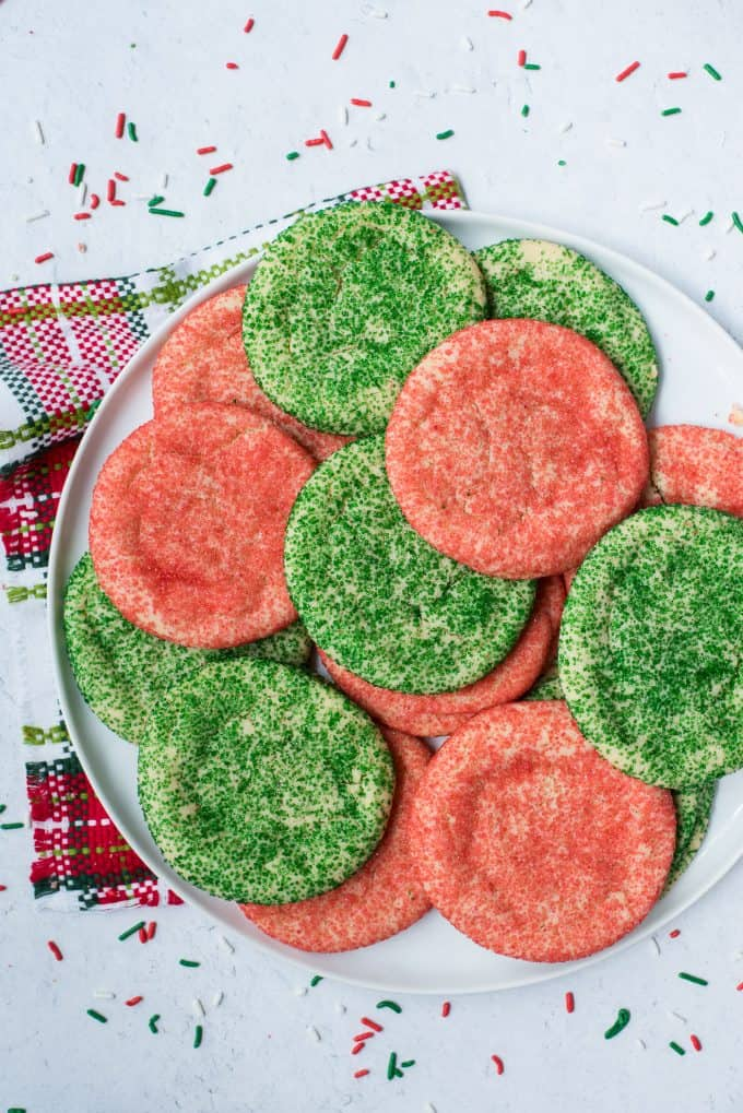 red and green christmas cookies arranged on white tray with Christmas napkin underneath