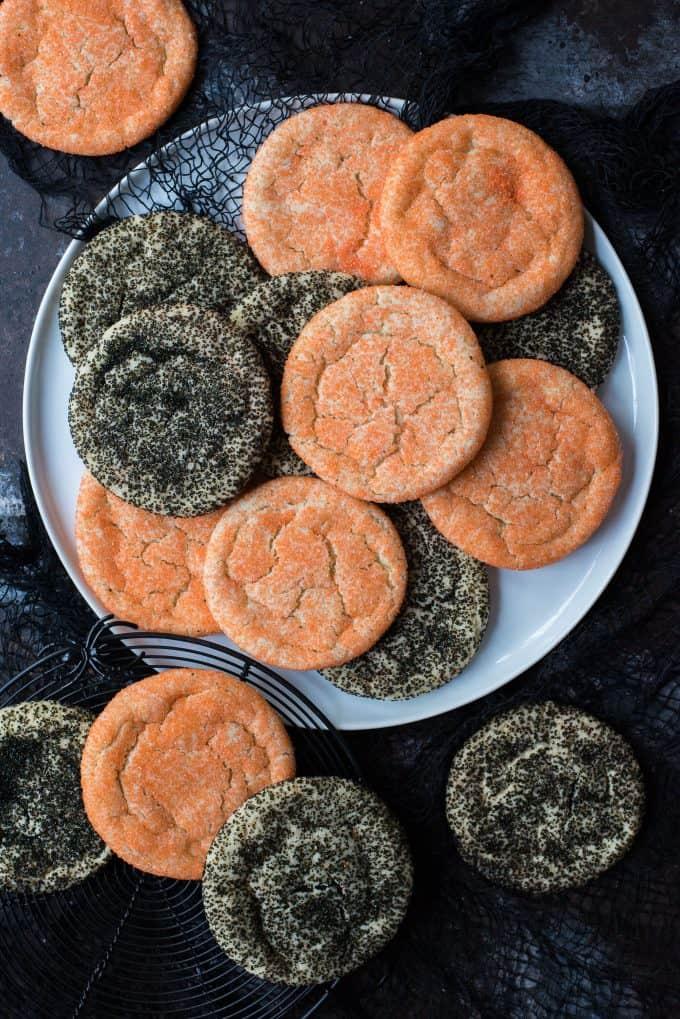 black and orange sugar cookies on white plate on black background