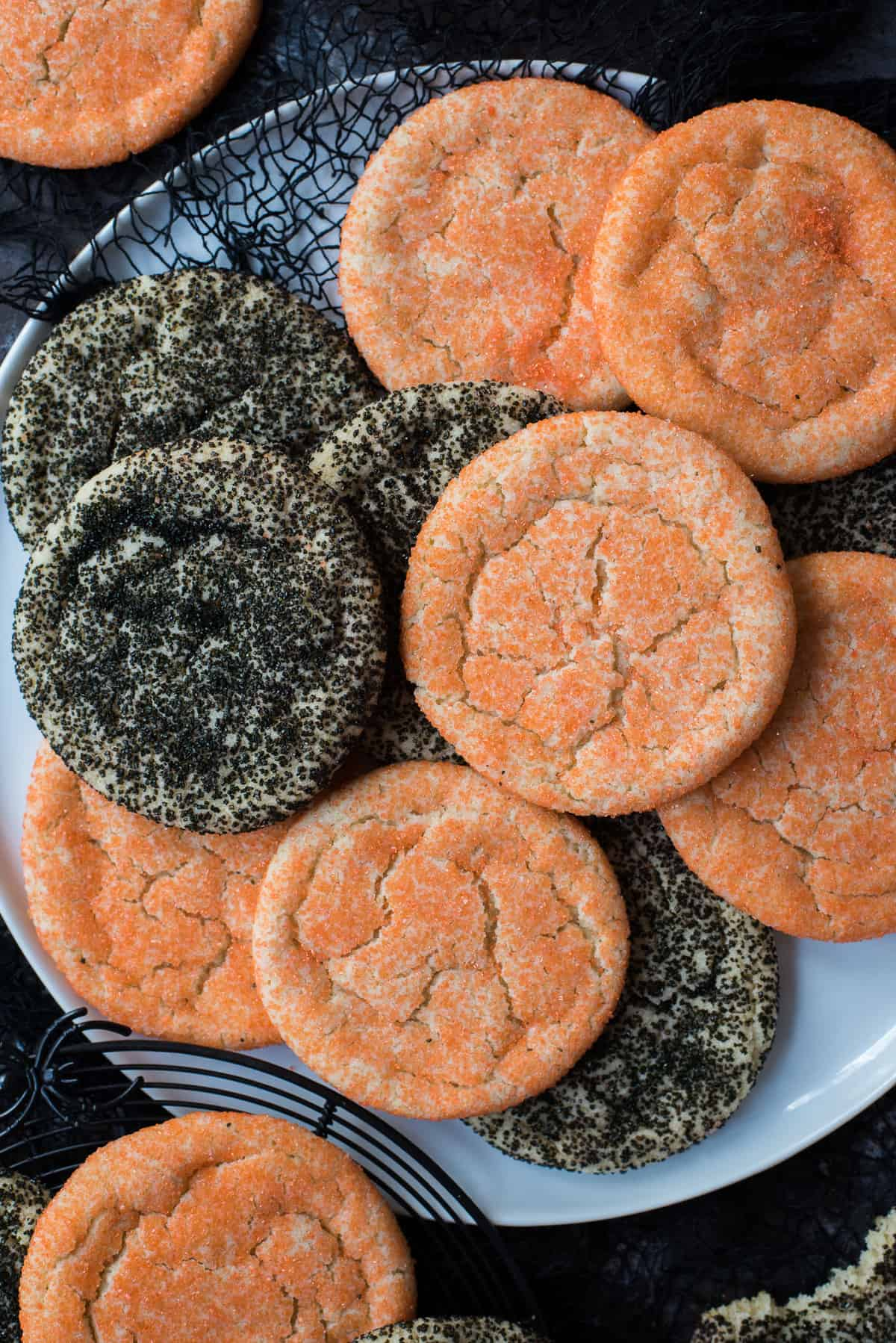 orange and black sugar cookies piled on white plate with black fabric on black background
