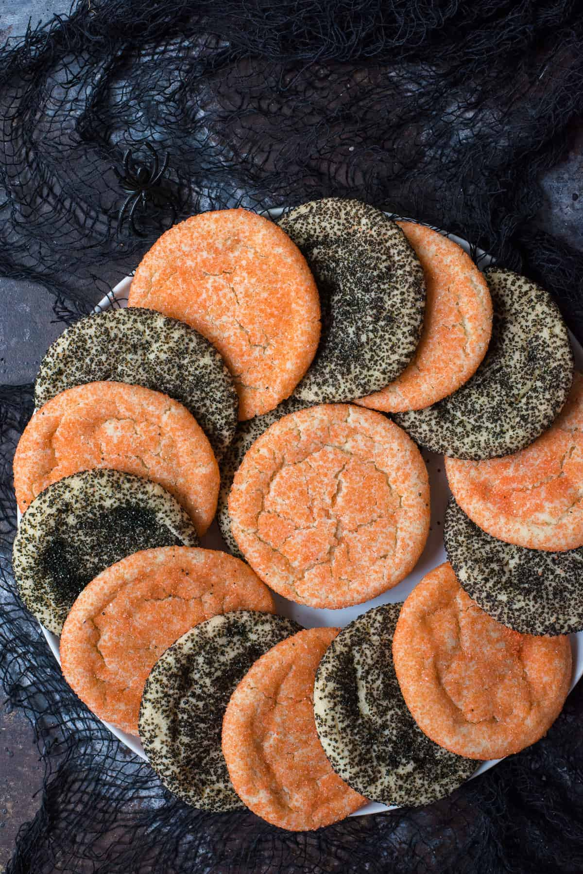 orange and black sugar cookies in a swirl pattern on white plate with black fabric on black background