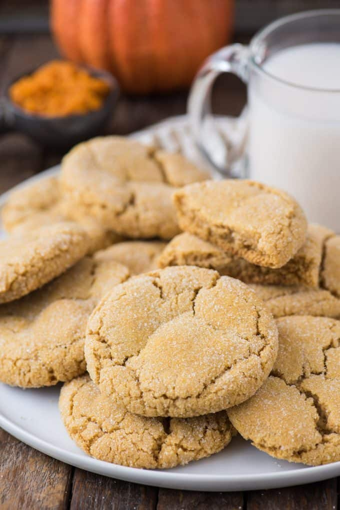 pumpkin cookies piled on white serving tray with a glass of milk and pumpkin in the background