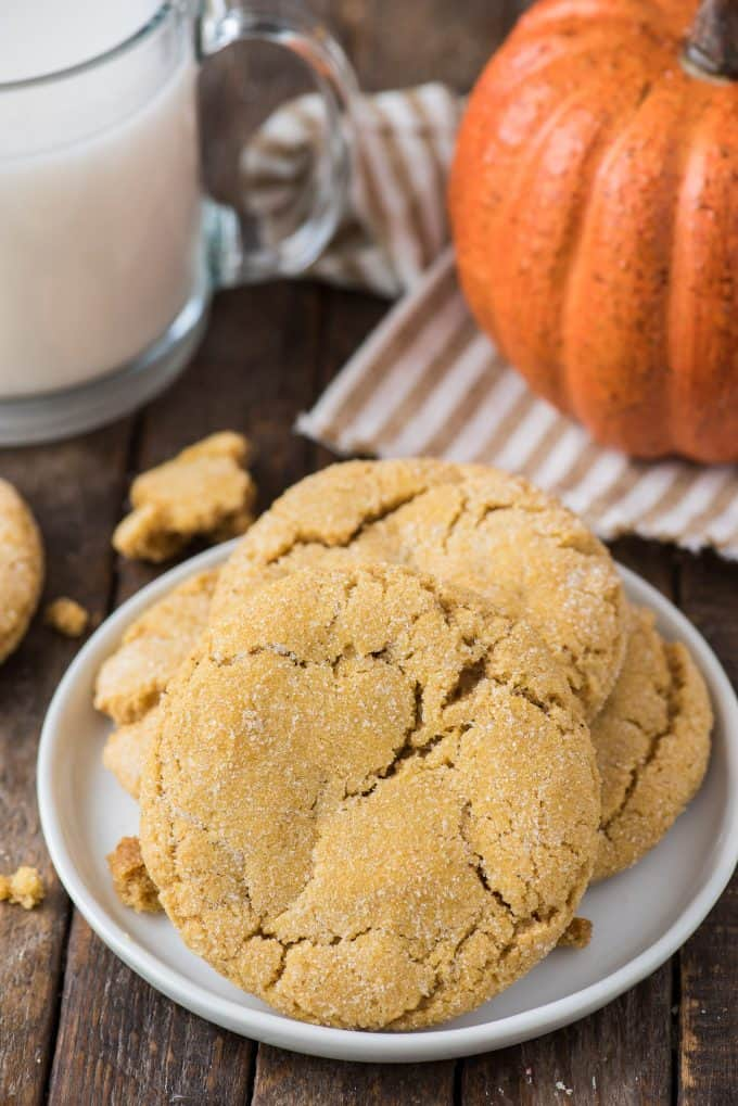 a few pumpkin sugar cookies on white plate with a glass of milk and pumpkin in the background
