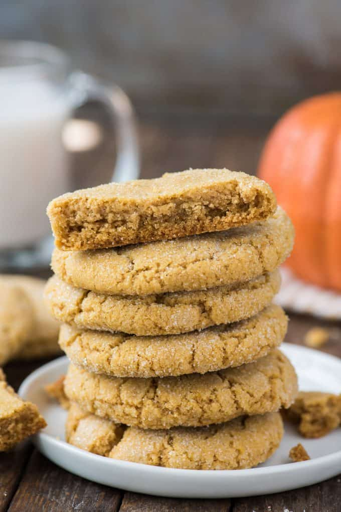 6 pumpkin cookies stacked in a tower on white plate with brown background