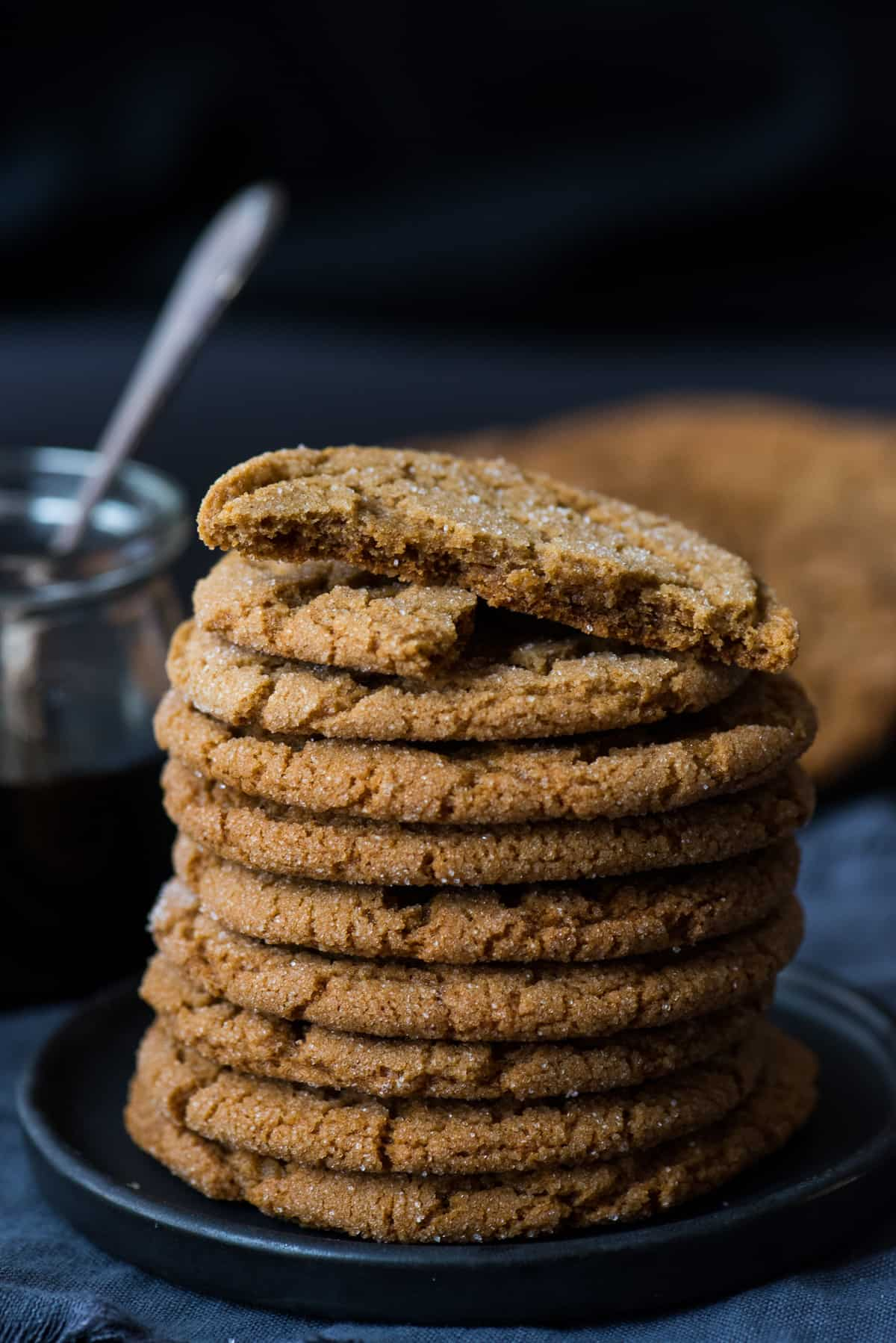 molasses cookies stacked on top of each other on dark plate on dark background with molasses in the background
