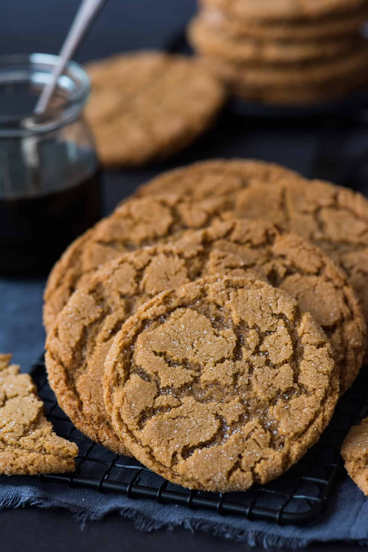 molasses ginger cookies on black wire rack on dark background with cookies and molasses in background