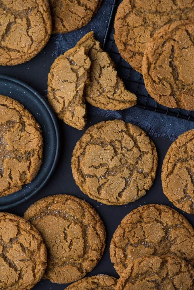 molasses crinkle cookies arranged on dark background with a dark plate and black wire tray