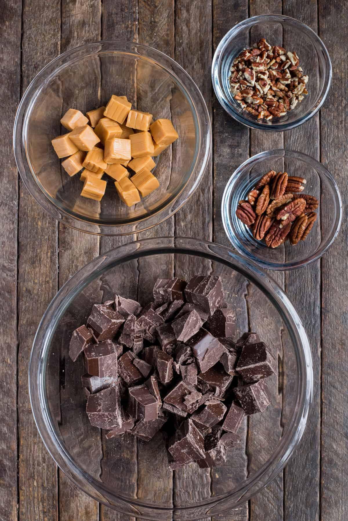 ingredients to make turtle bark in glass bowls on dark wood background