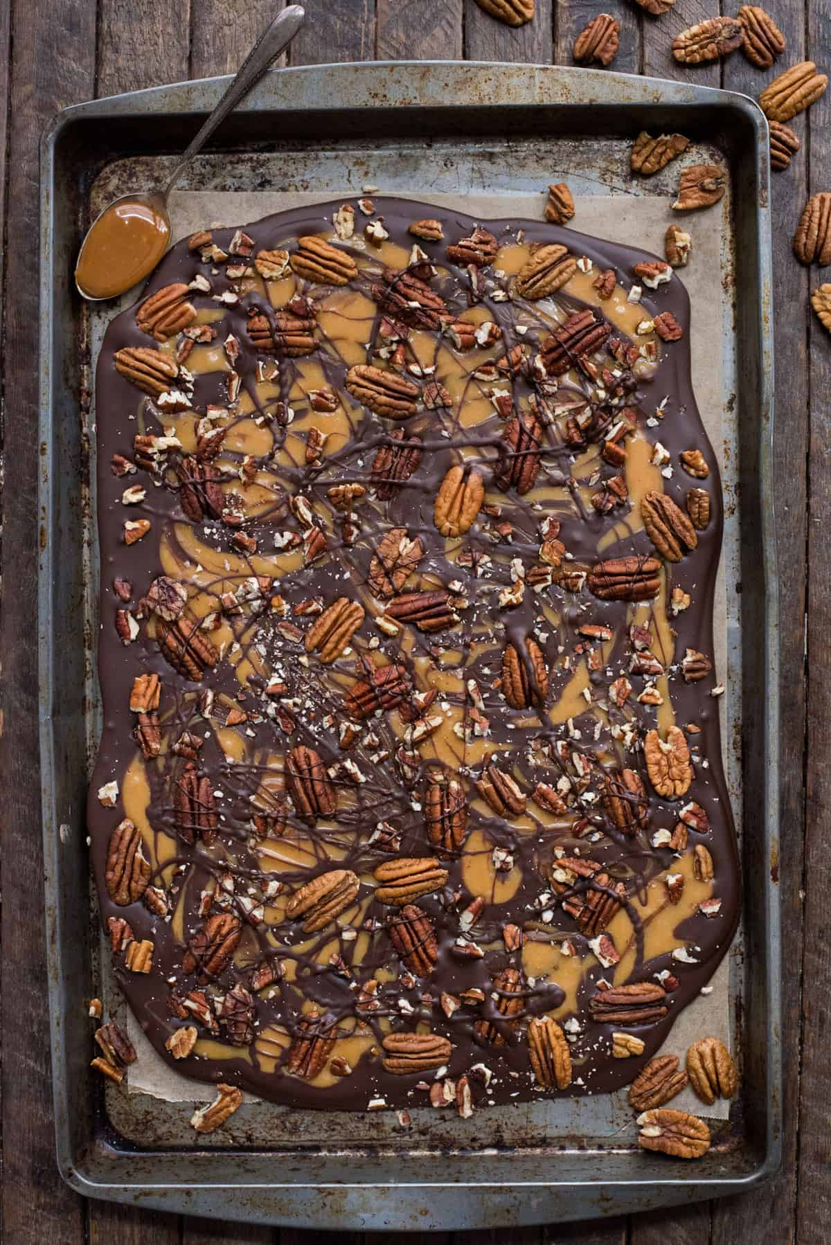 chocolate caramel pecan turtle bark slab on metal baking sheet