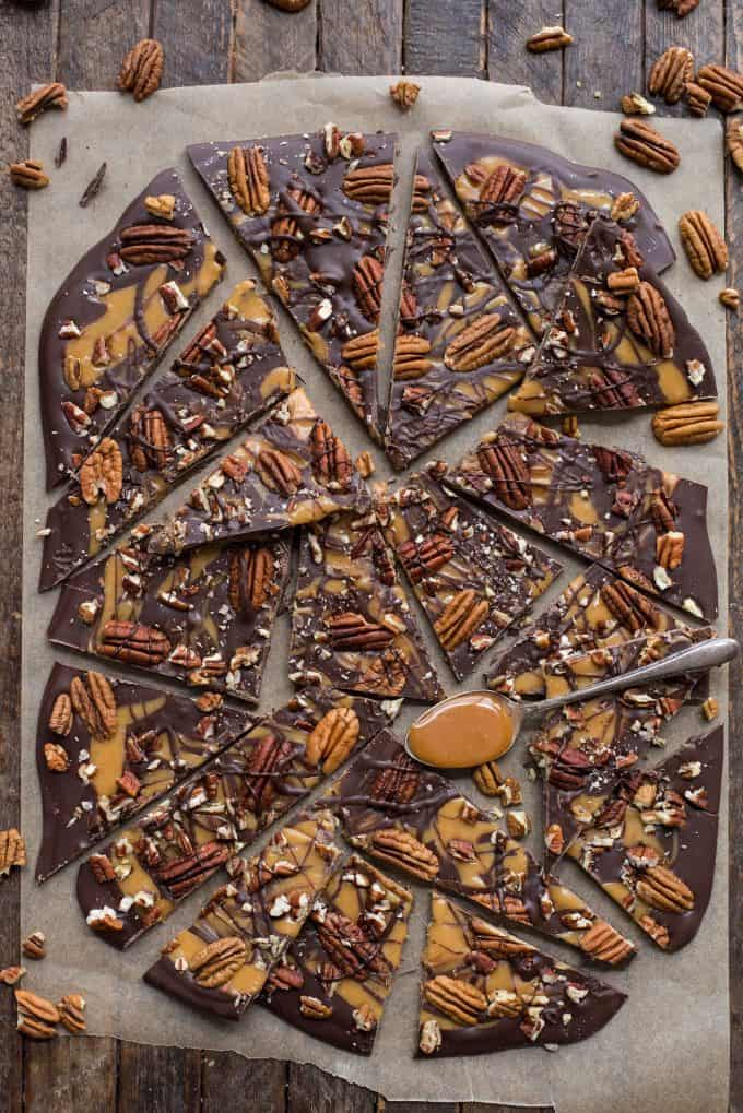 turtle bark with chocolate, caramel and pecans broken into pieces on brown parchment paper
