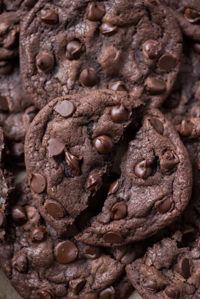 close up of one double chocolate chip cookie broken in half with gooey chocolate chips