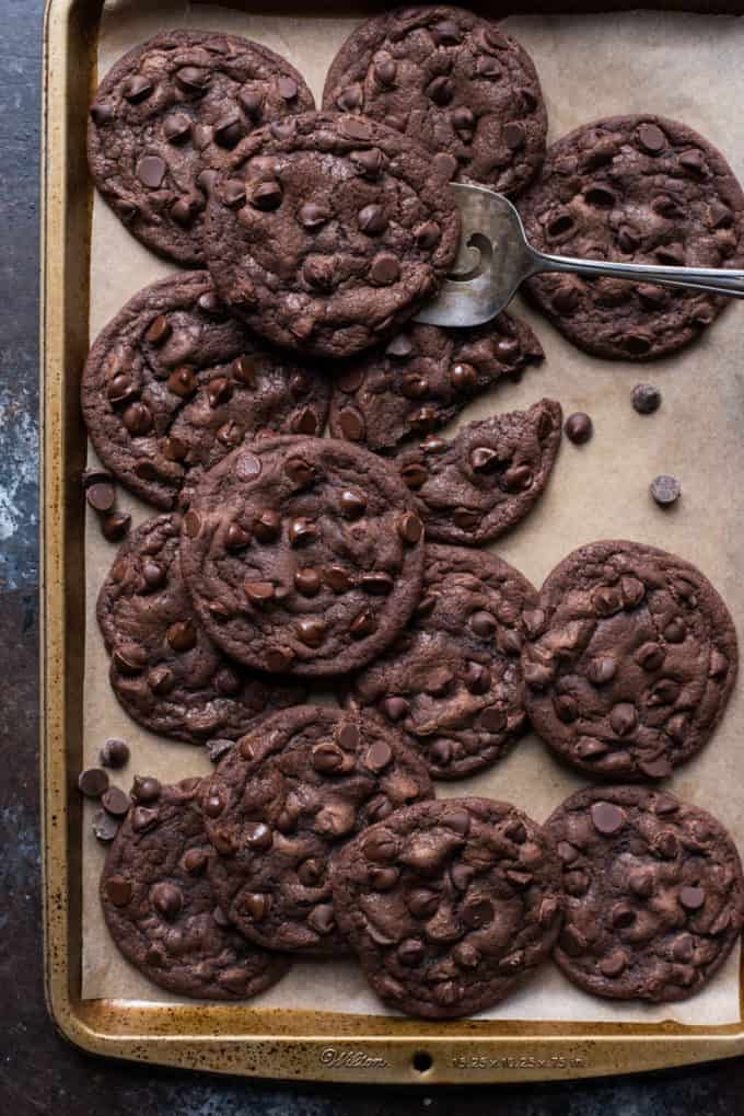 double chocolate chip cookies arranged on brown parchment paper with metal cookie spatula under one cookie