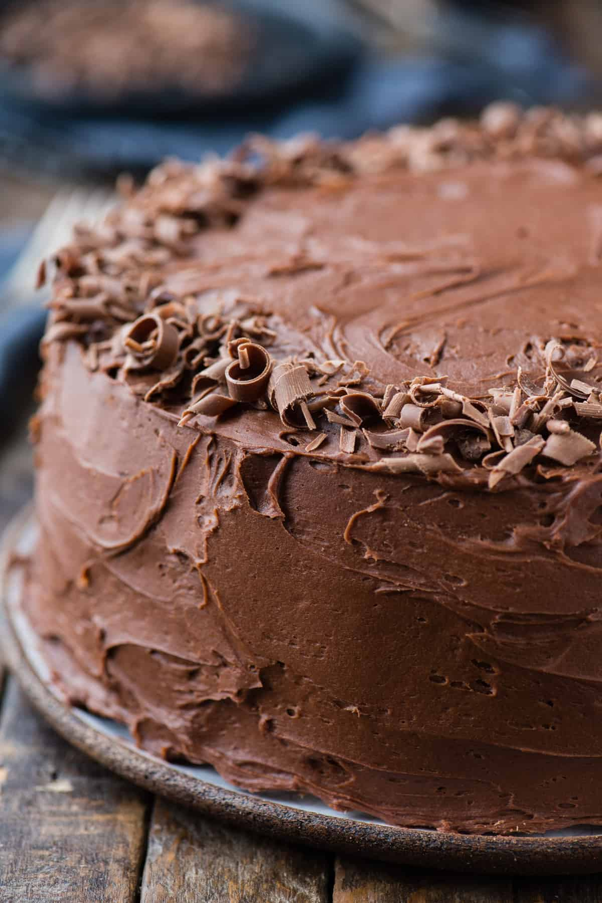 close up of homemade chocolate cake with chocolate shavings sprinkled around the edge of the cake