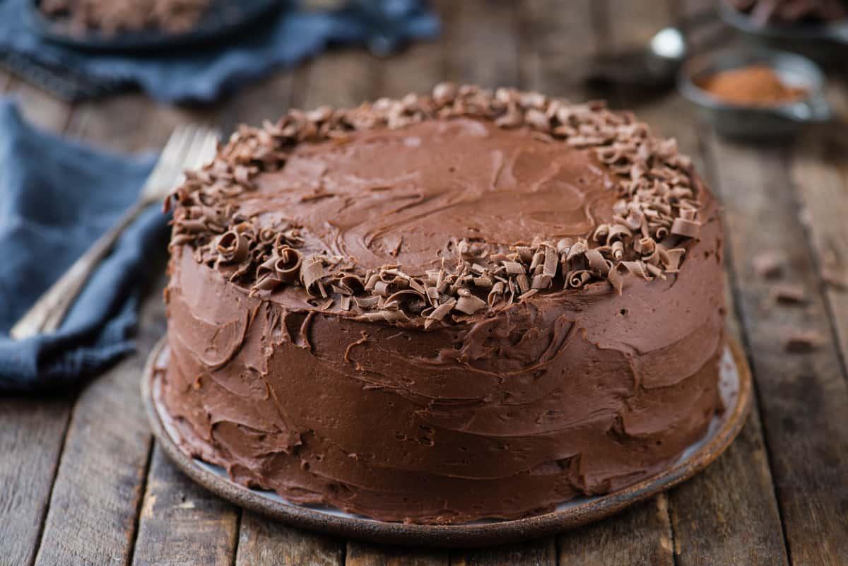 whole chocolate cake with chocolate shavings around the edge on wood background