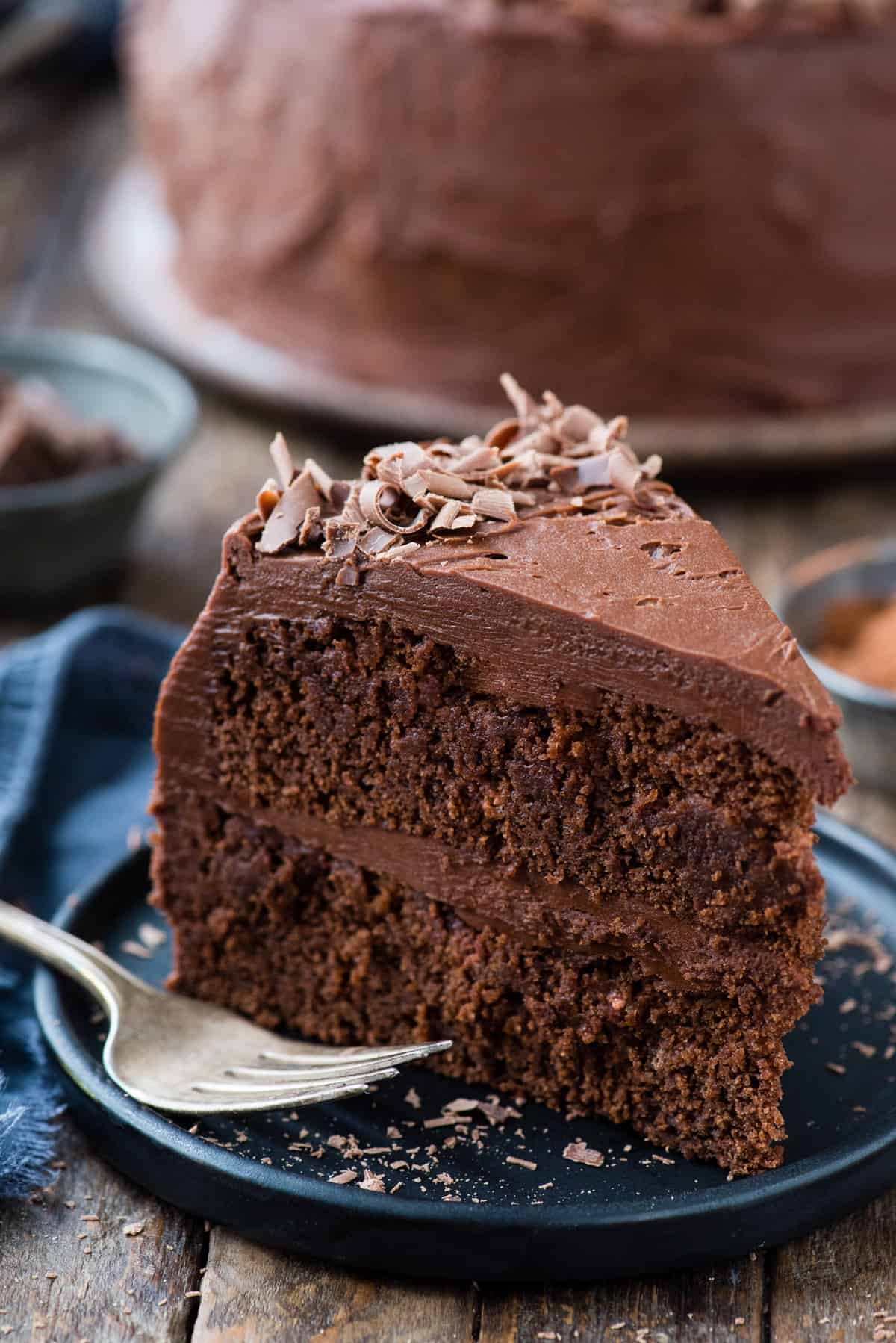 slice of chocolate cake standing up on dark blue plate on wood background