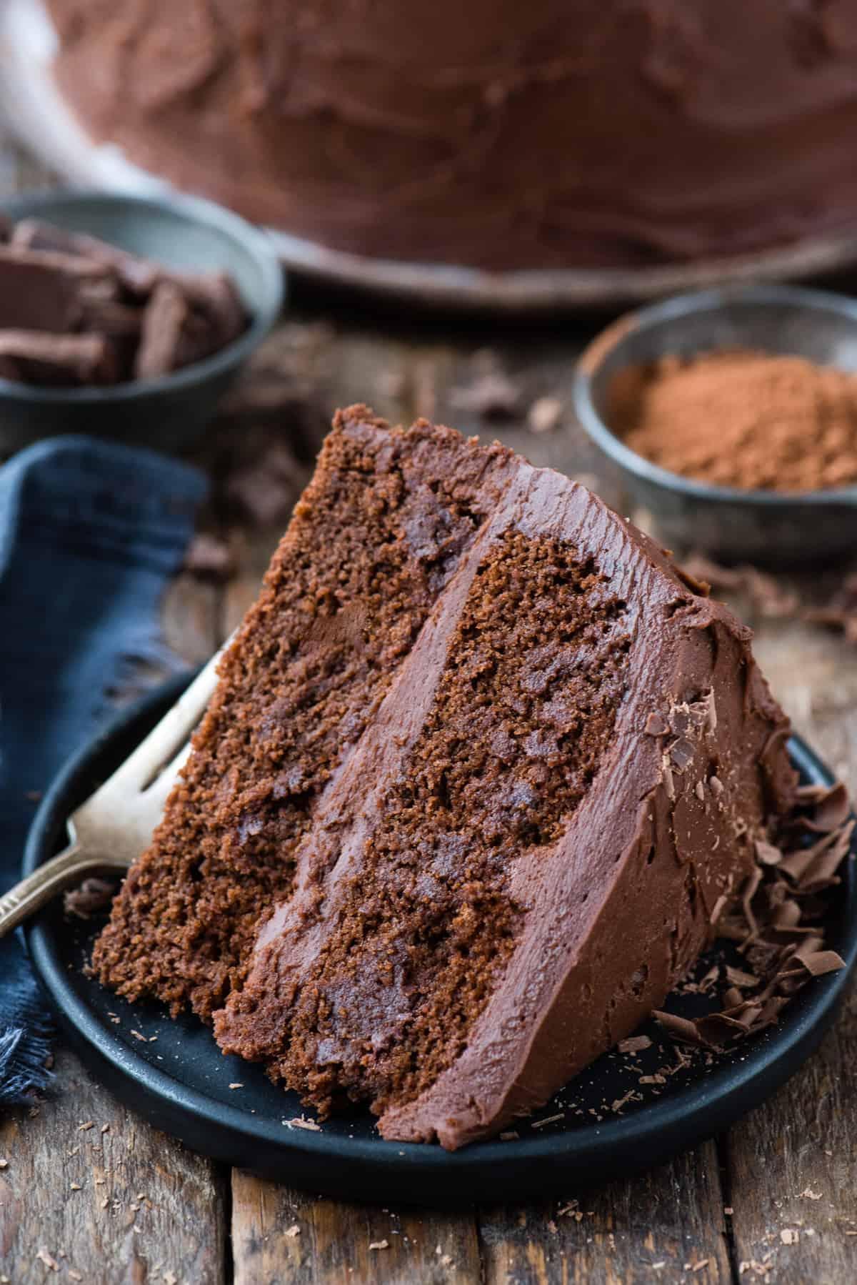 slice of chocolate cake on its side on dark blue plate on wood background