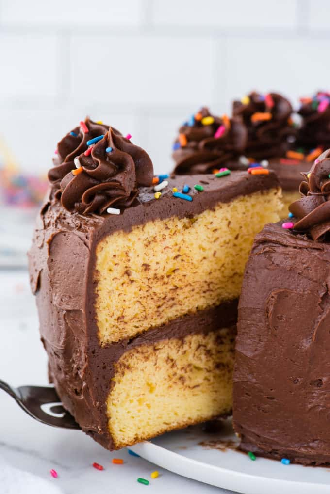 slice of yellow cake with chocolate frosting being removed from cake