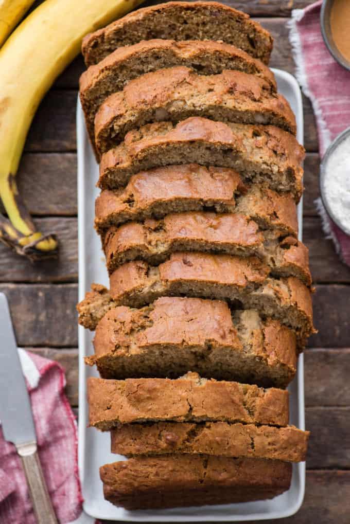 sliced banana bread on white platter on wood background