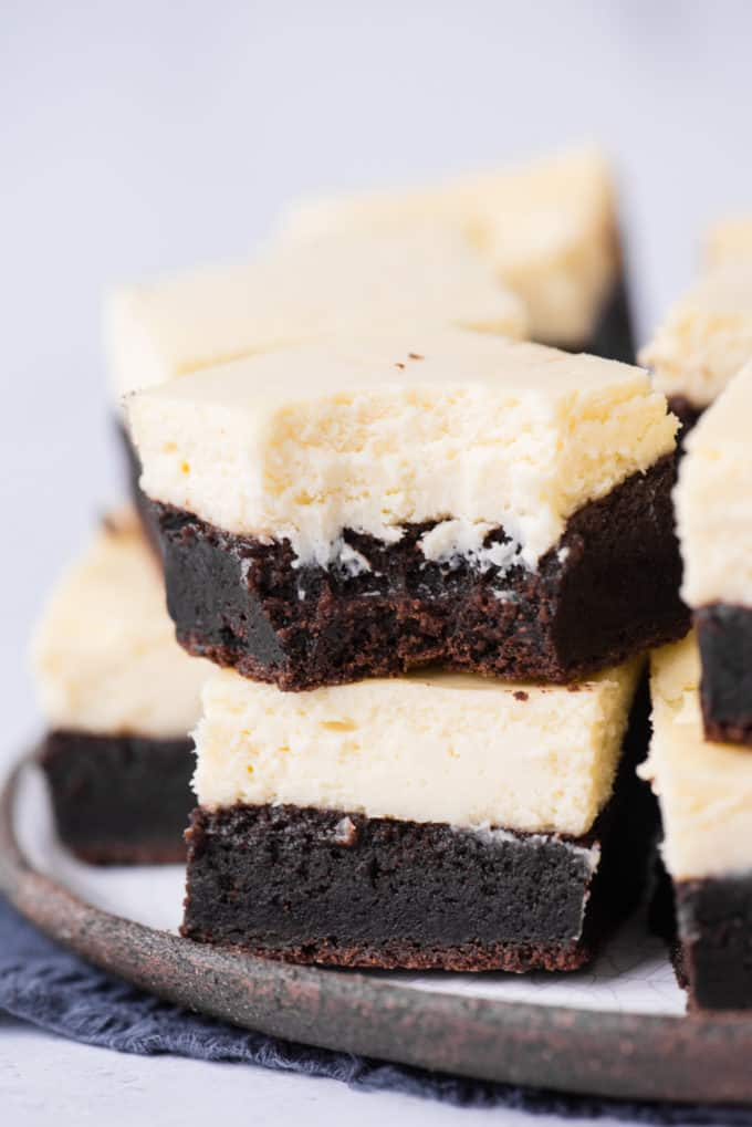 two cheesecake brownies stacked on each other, top brownie has bite removed on white plate