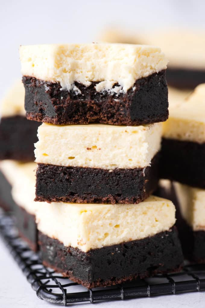 three cheesecake brownies stacked on each other, top brownie has bite removed on black wire rack on white background