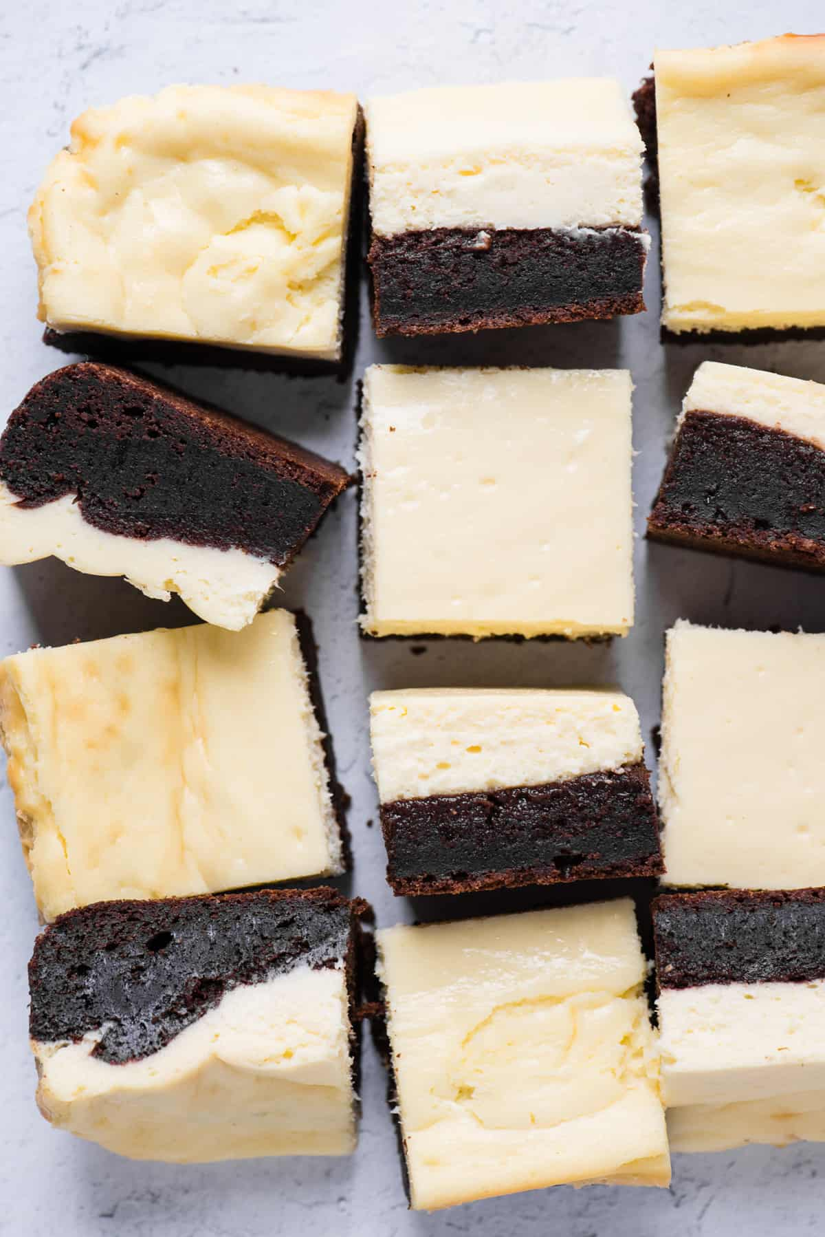 cheesecake brownies cut into squares and arranged randomly on white background