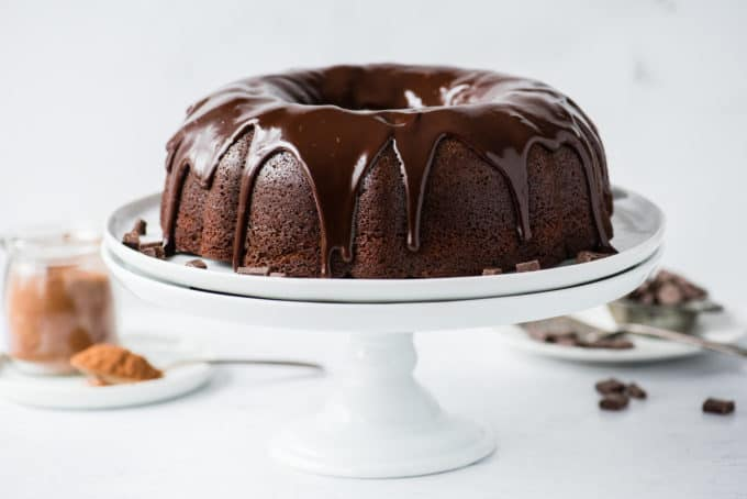 whole chocolate bundt cake with chocolate glaze on white cake stand on white background