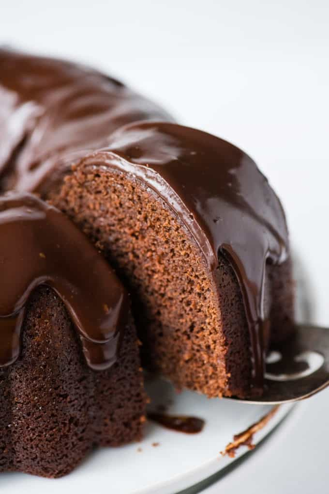 slice of chocolate bundt cake with chocolate glaze being removed from the cake on metal spatula on white background