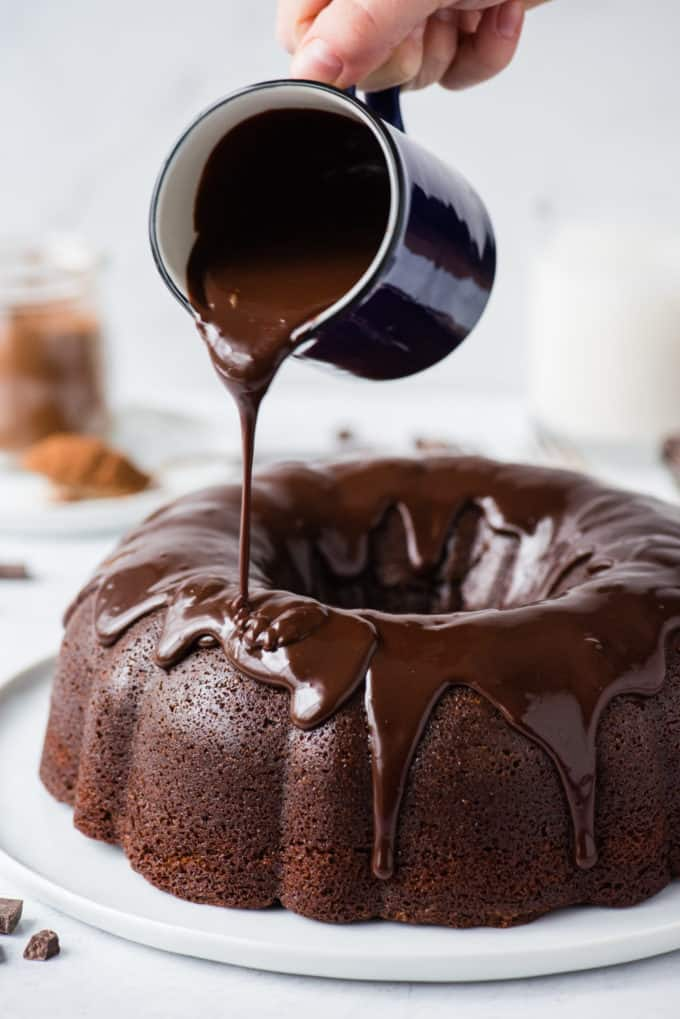 chocolate glaze being poured over chocolate bundt cake on white plate on white background