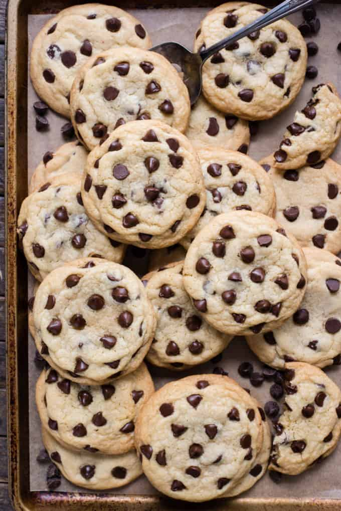 chocolate chip cookies arranged on a metal baking sheet with brown parchment paper