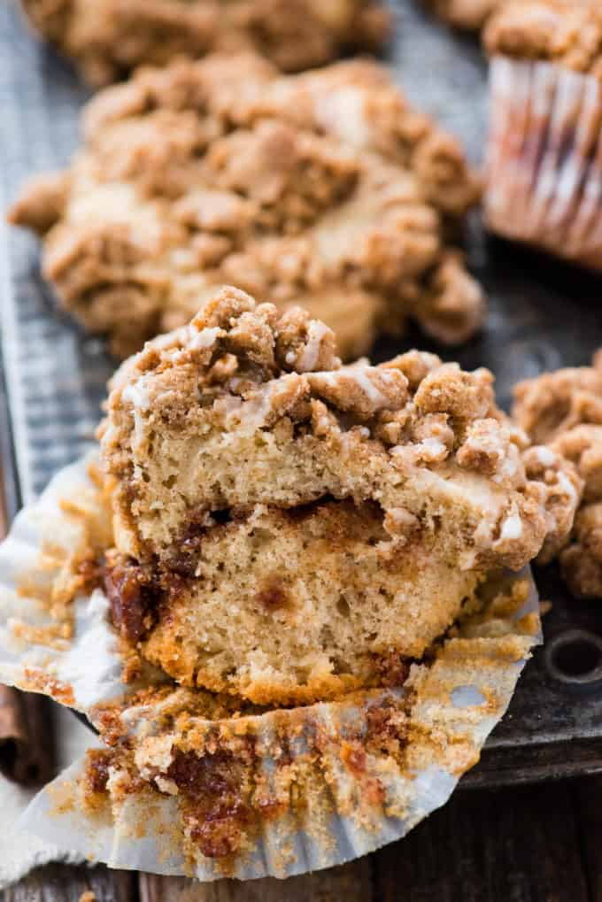 coffee cake muffin cut in half with a ribbon of cinnamon sugar baked in with crumb topping on metal muffin pan