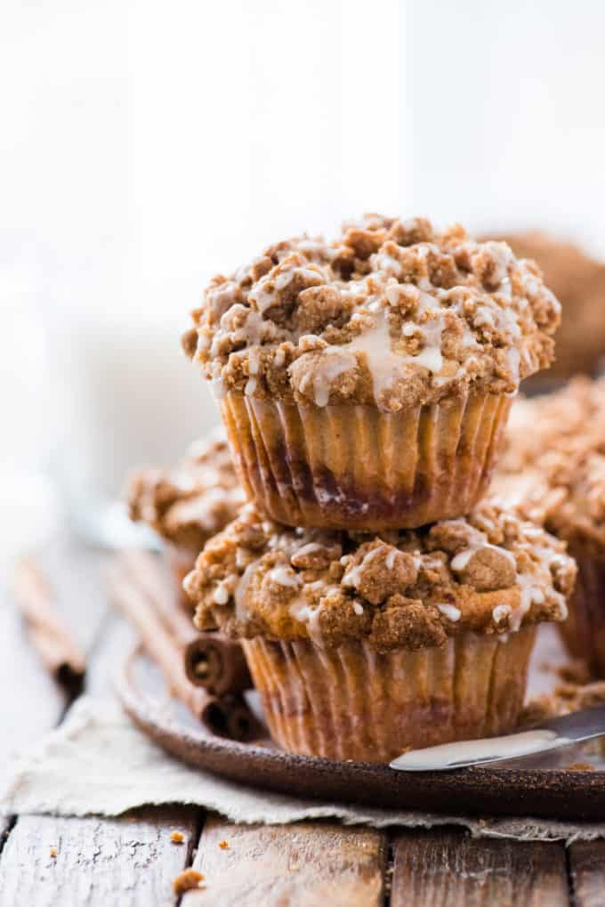 two coffee cake muffins with crumb topping stacked on top of each other on wood background