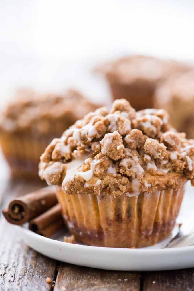 coffee cake muffin with crumb topping on white plate on wood background