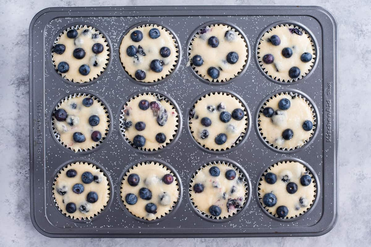 blueberry muffin batter in metal muffin pan